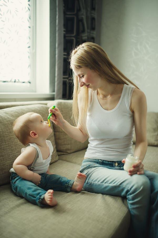 Bebê de alimentação da mãe com uma colher imagens de stock royalty free