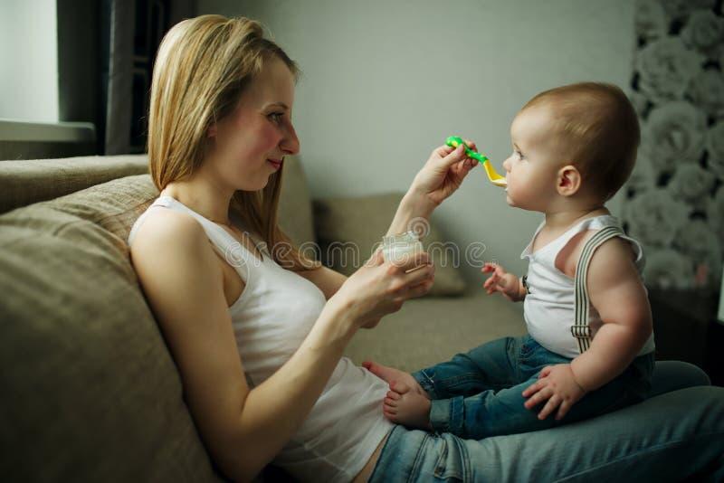 Bebê de alimentação da mãe com uma colher foto de stock royalty free
