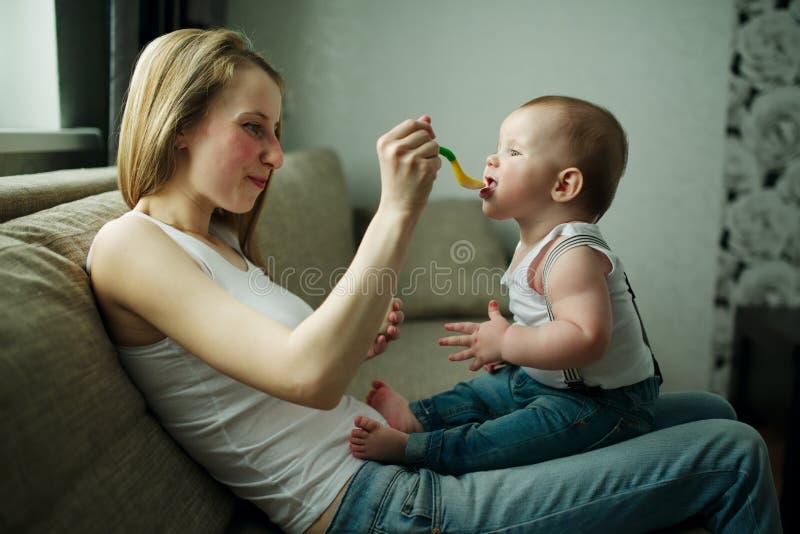 Bebê de alimentação da mãe com uma colher foto de stock