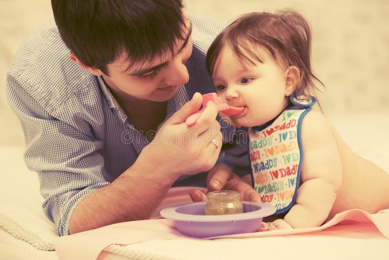 Bebê de alimentação do pai feliz em casa fotografia de stock