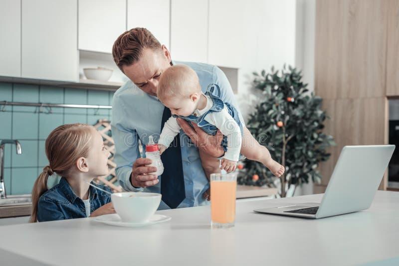 Bebê de apoio do pai agradável bonito e guardar uma garrafa imagem de stock royalty free