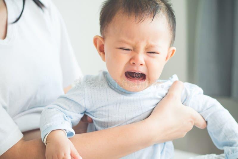 Bebê de grito na mão da sua mãe no quarto/ imagem de stock