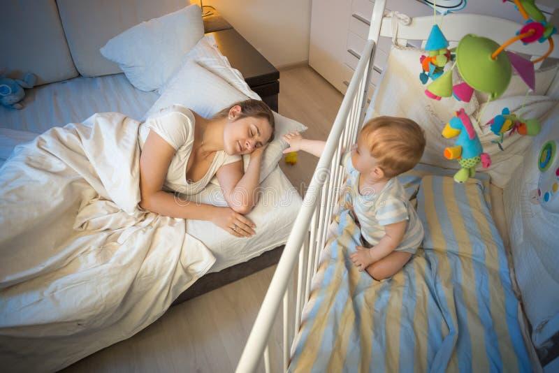 Bebê de grito que acorda e que alcança sua mãe na noite fotografia de stock