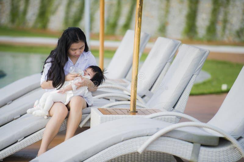 Bebê de nutrição novo da filha da mulher chinesa asiática feliz e bonito com a garrafa da fórmula na piscina tropical do recurso  imagens de stock royalty free