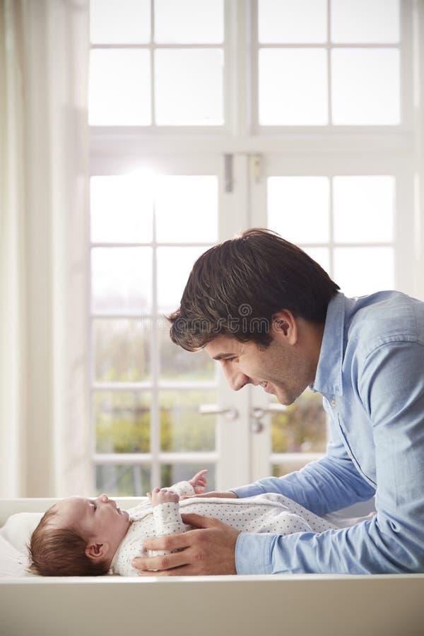 Bebê de Playing With Newborn do pai que encontra-se na tabela em mudança imagens de stock