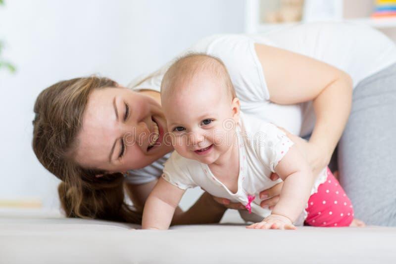 Bebê de rastejamento engraçado com mãe em casa imagens de stock