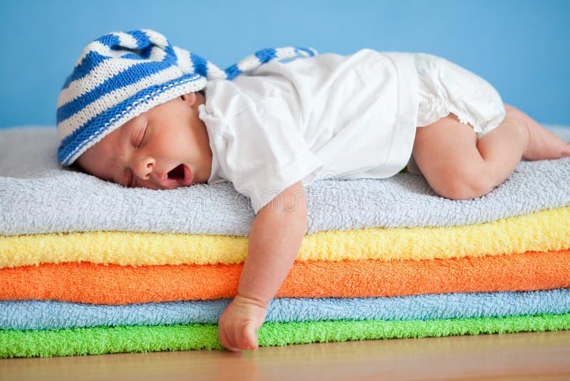 Bebê de sono de bocejo na pilha colorida de toalhas fotos de stock royalty free