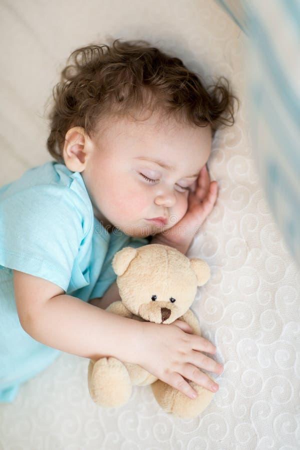 Bebê de sono na cama, guardando um urso de peluche fotografia de stock