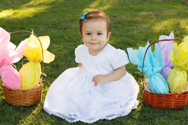 Bebê de sorriso bonito na grama verde com os ovos de chocolate da Páscoa imagem de stock