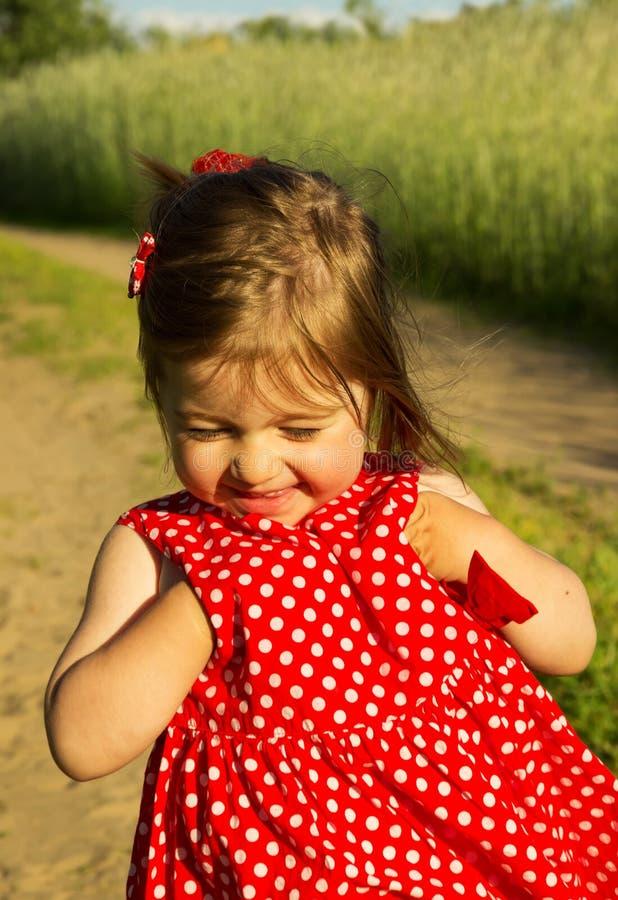 Bebê de sorriso bonito no vestido vermelho no dia de verão foto de stock royalty free