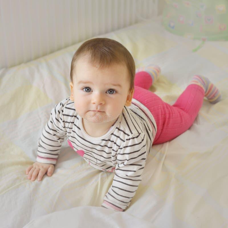 Bebê de sorriso bonito que encontra-se na cama imagens de stock royalty free
