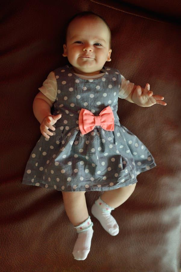 Bebê de sorriso bonito que encontra-se na cama foto de stock