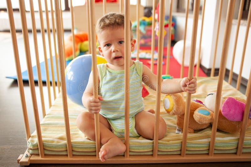 Bebê de sorriso bonito que olha através das barras de madeira de sua ucha ou fotografia de stock royalty free