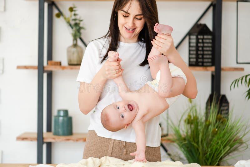 Bebê de sorriso de cabeça para baixo da posse nova da mãe fotografia de stock royalty free