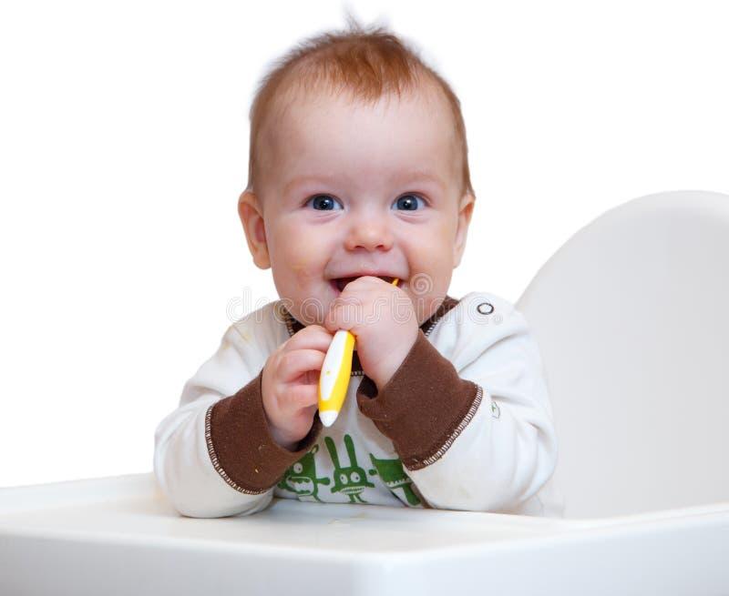 Bebê de sorriso com a colher em suas mãos foto de stock royalty free