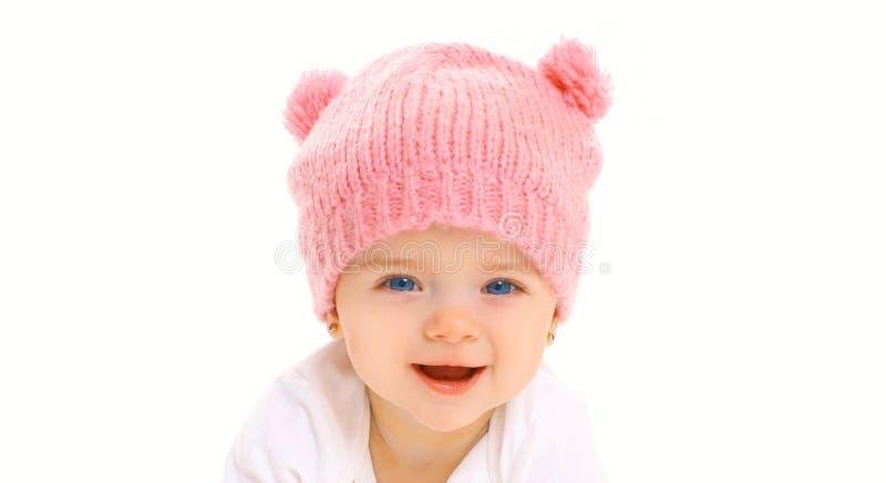 Bebê de sorriso feliz da cara do close-up do retrato no chapéu cor-de-rosa feito malha no branco imagem de stock royalty free