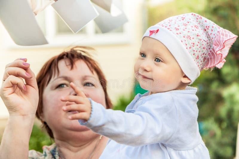 Bebê de sorriso feliz que joga com avó alegre fora Junto estão travando as lista de papel do voo fotos de stock royalty free