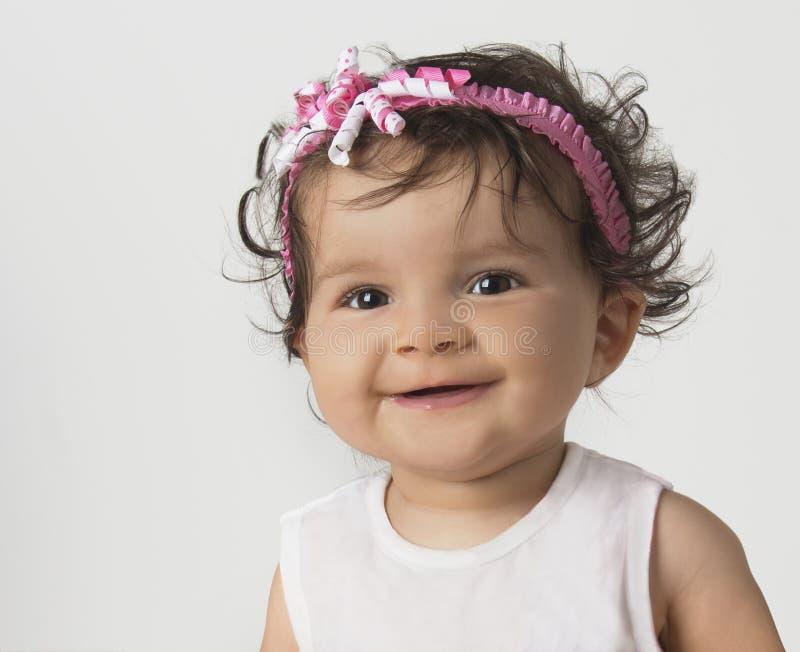 Bebê de sorriso na faixa cor-de-rosa fotografia de stock