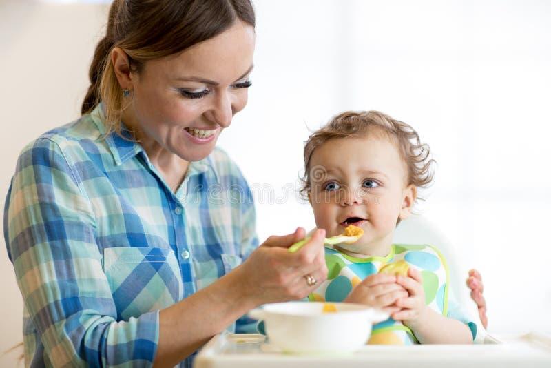 Bebê de sorriso que come o alimento com a mamã na cozinha fotos de stock royalty free