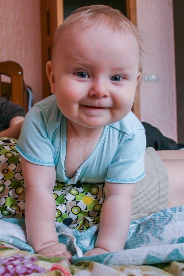 Bebê de sorriso que encontra-se em sua mãe e que olha à câmera Bebê na cama com pais foto de stock royalty free