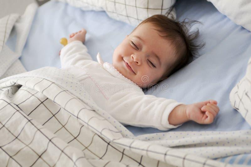 Bebê de sorriso que encontra-se em um sono da cama imagens de stock