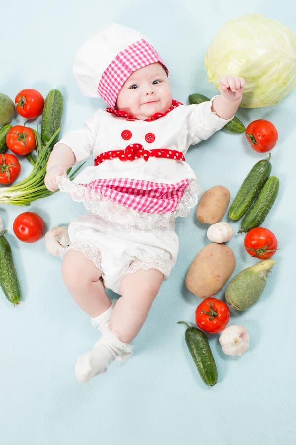 Bebê de sorriso que veste um chapéu do cozinheiro chefe cercado por vegetais imagem de stock