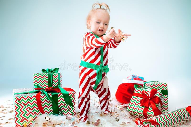 Bebê de um ano bonito do bebê que veste o chapéu de Santa que levanta sobre o fundo do Natal Assento no assoalho com bola do Nata fotos de stock royalty free