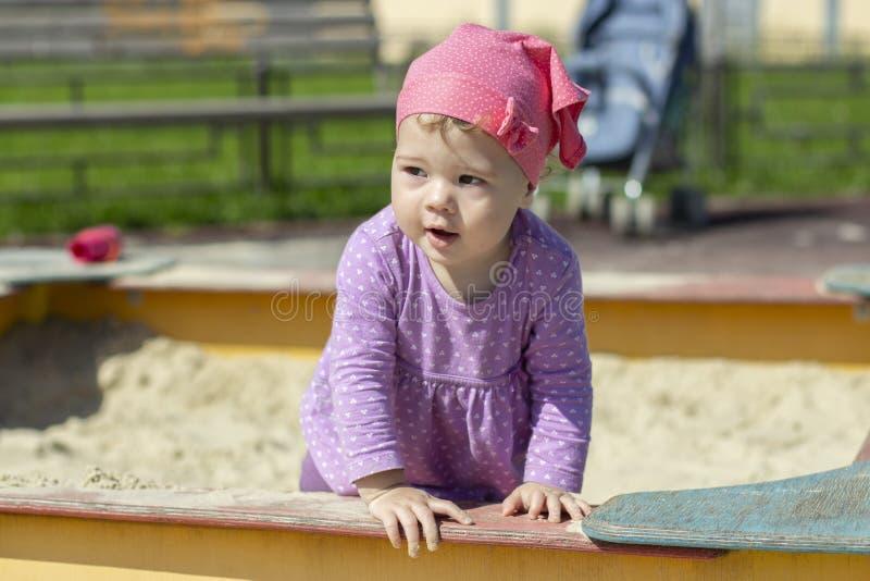 Bebê de um ano da menina em olhares do vestido e do lenço ao lado alegremente Close-up horizontal imagem de stock