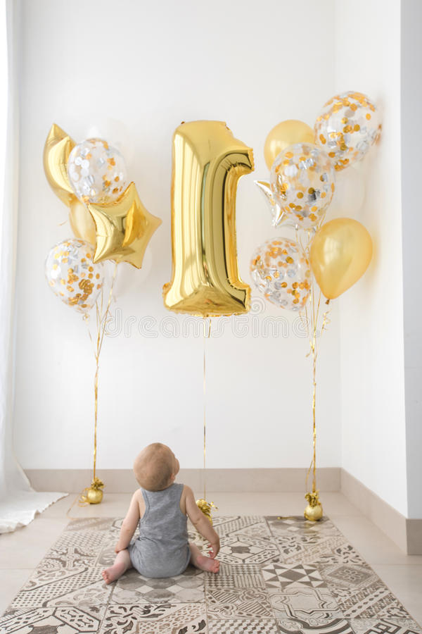 Bebê de um ano do aniversário do ` dos bebês primeiro com balões foto de stock