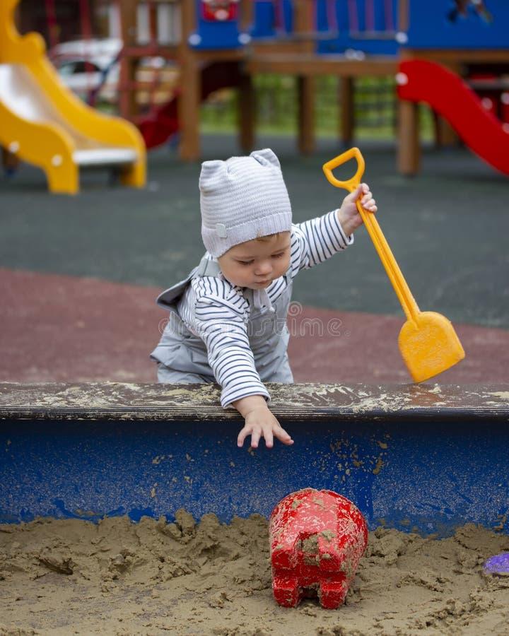 Bebê de um ano do menino do bebê em calças impermeáveis nas correias que jogam na caixa de areia com brinquedos Pouco bebê em uma foto de stock