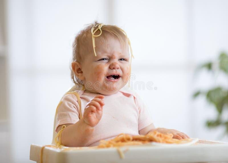 Bebê desarrumado bonito que grita ao comer a massa em casa imagem de stock