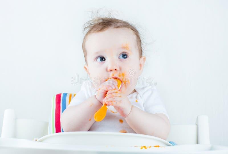 Bebê desarrumado doce que come uma cenoura em uma cadeira alta branca imagem de stock