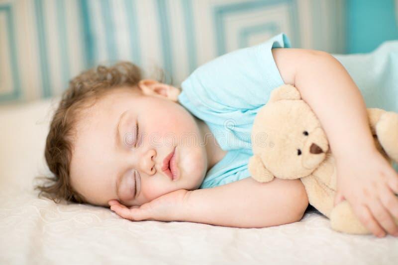 Bebê despreocupado do sono com o brinquedo macio na cama imagens de stock