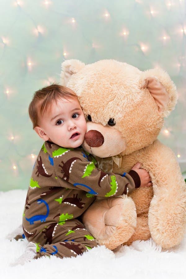 Bebê do Natal nos pijamas que prendem o urso de peluche fotografia de stock