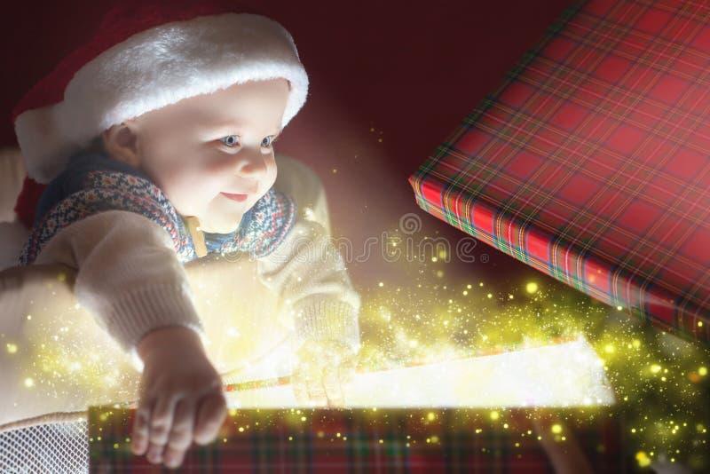 Bebê do Natal que abre um presente e uma caixa de presente foto de stock