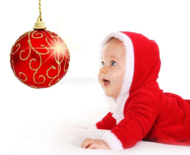 Bebê do Natal que olha uma esfera vermelha sparkling fotografia de stock royalty free