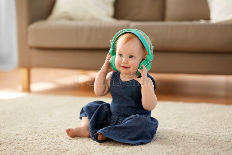 Bebê do ruivo nos fones de ouvido que escuta a música imagem de stock royalty free