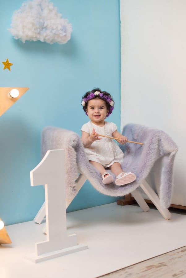 Bebê doce de sorriso feliz que senta-se na poltrona com brilho da estrela clara, menina do aniversário, criança de um ano foto de stock royalty free