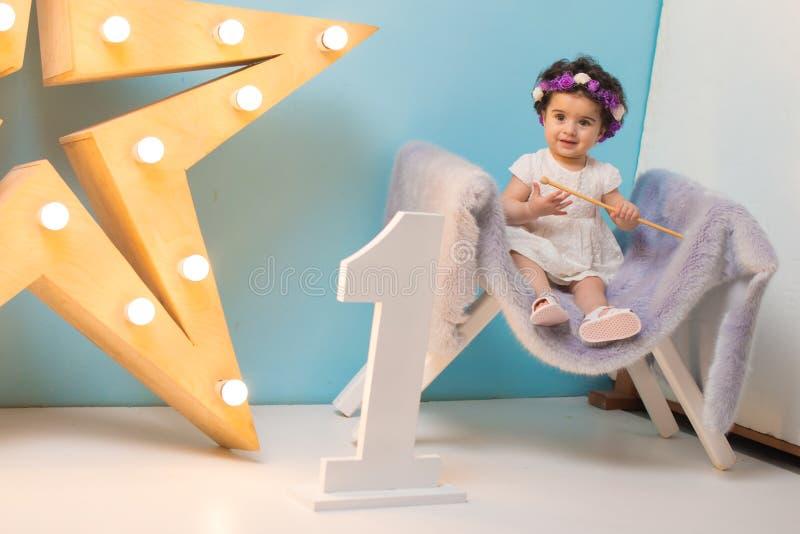 Bebê doce de sorriso feliz que senta-se na poltrona com brilho da estrela clara, menina do aniversário, criança de um ano imagem de stock