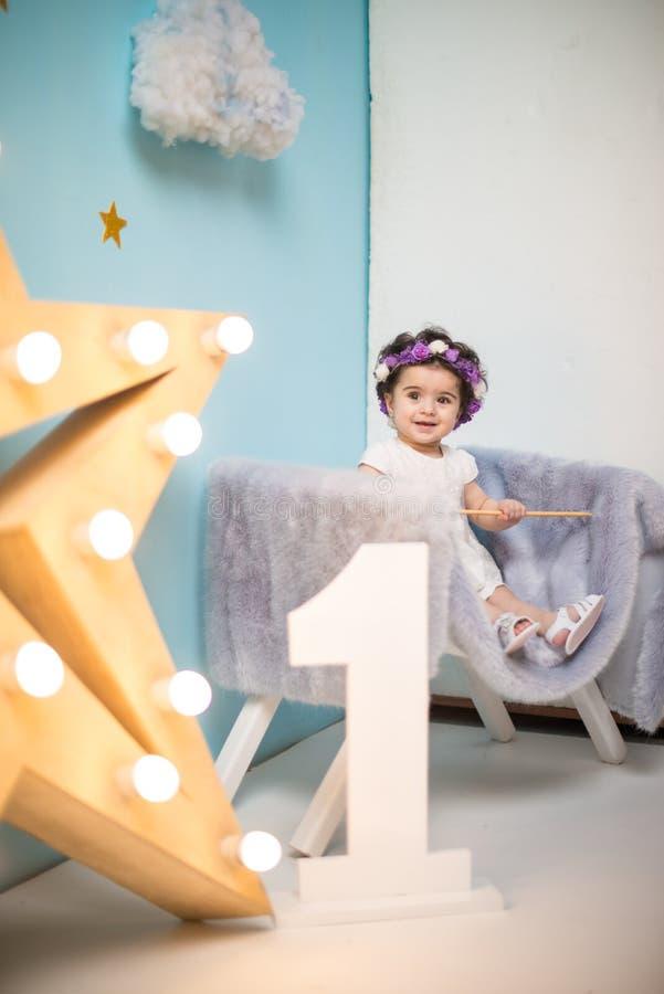 Bebê doce de sorriso feliz que senta-se na poltrona com brilho da estrela clara, menina do aniversário, criança de um ano fotografia de stock royalty free