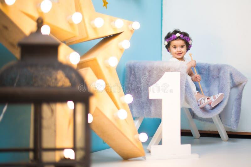 Bebê doce de sorriso feliz que senta-se na poltrona com brilho da estrela clara, menina do aniversário, criança de um ano fotografia de stock
