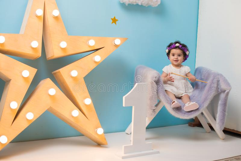 Bebê doce de sorriso feliz que senta-se na poltrona com brilho da estrela clara, menina do aniversário, criança de um ano foto de stock
