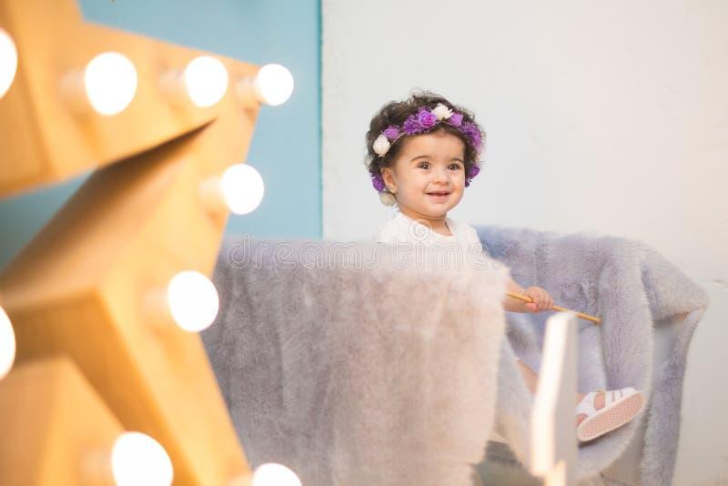 Bebê doce de sorriso feliz que senta-se na poltrona com brilho da estrela clara, menina do aniversário, criança de um ano fotos de stock