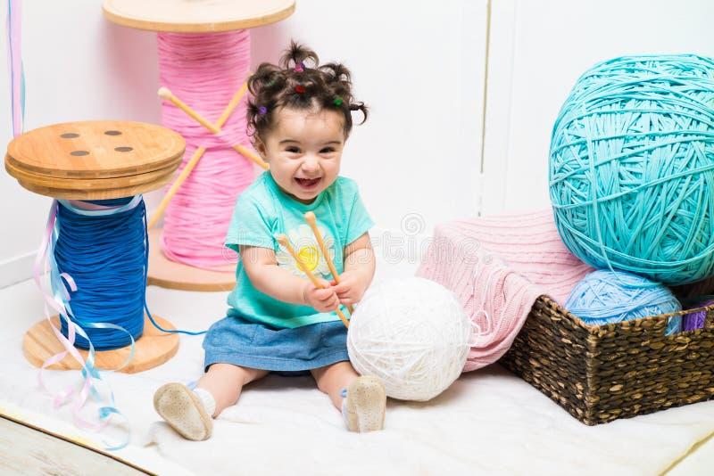 Bebê doce de sorriso feliz que senta-se no sofá, menina do aniversário, criança de um ano fotografia de stock