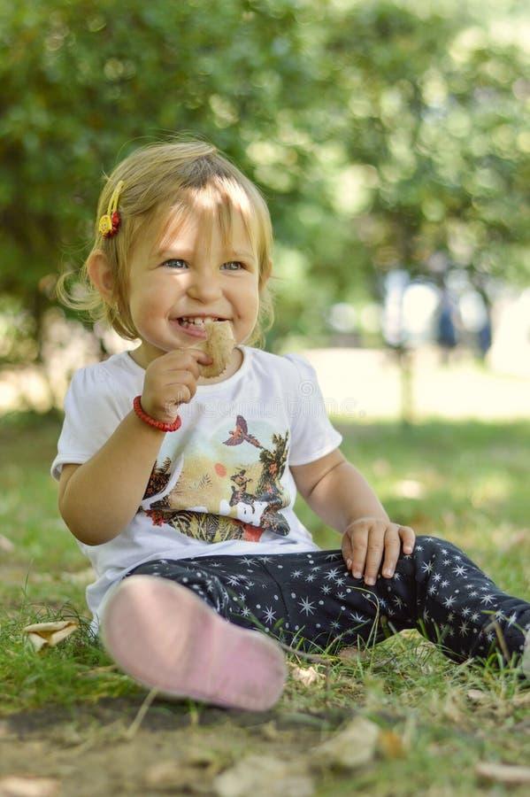 Bebê doce do bebê de um ano dos olhos azuis que senta-se na grama em uma paridade imagens de stock royalty free