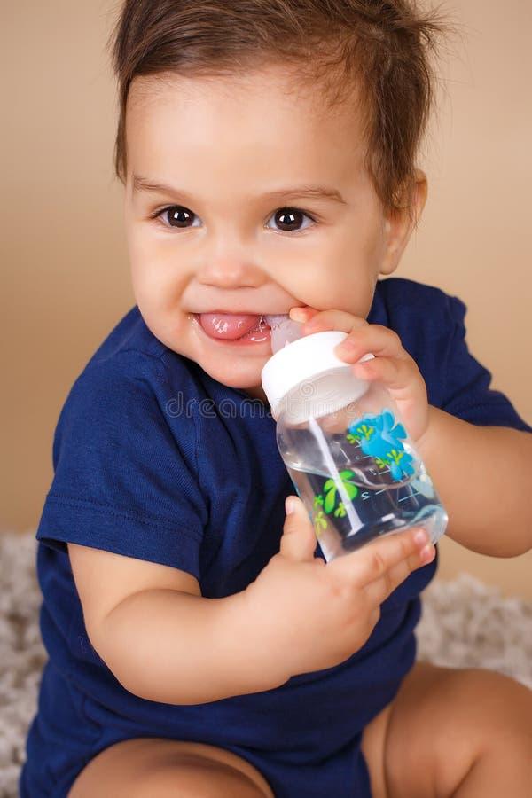 Bebê doce que guarda a garrafa e a água potável imagens de stock royalty free