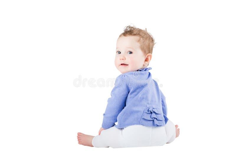 Bebê doce que senta-se e que olha sobre seu ombro fotos de stock royalty free