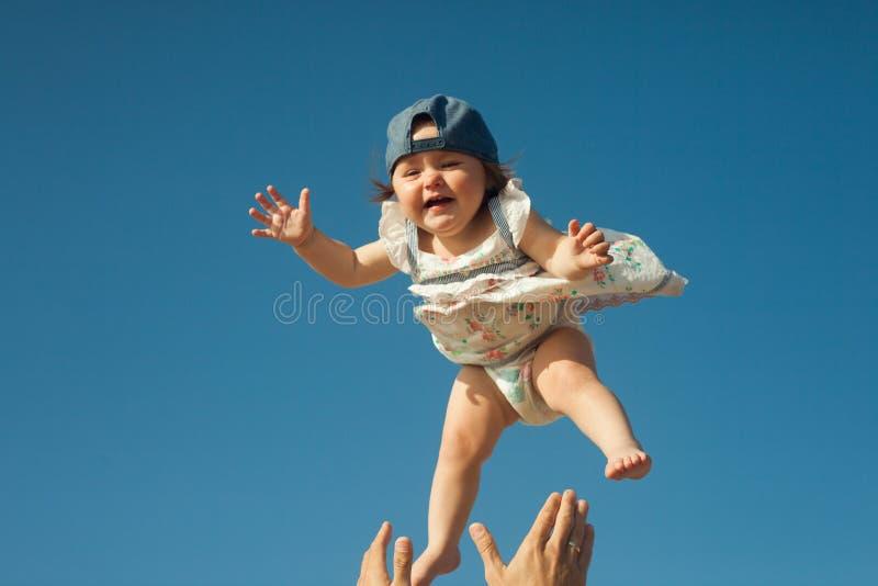 Bebê e céu no fundo em um dia ensolarado Pai considerável novo que sustenta sua filha bonito pequena fotos de stock