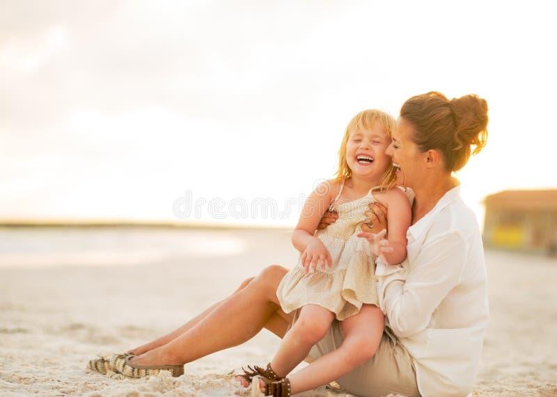 Bebê e mãe de sorriso que sentam-se na praia foto de stock
