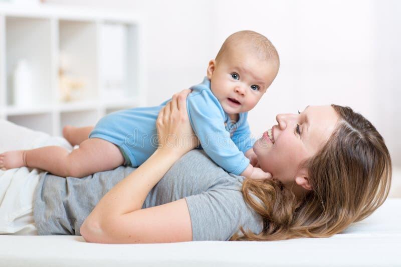 Bebê e mãe do smiley que encontra-se na cama imagens de stock